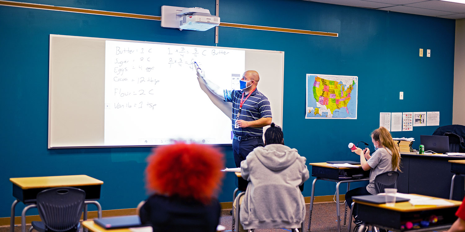 Math teacher writing on white board in front of a middle school class of students.