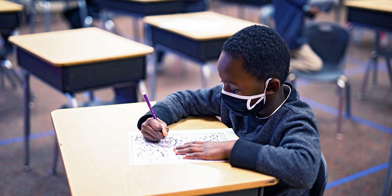 Student completing worksheet at their desk.