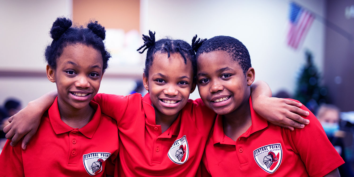 Smiling elementary students in Central Point Preparatory Academy shirts.