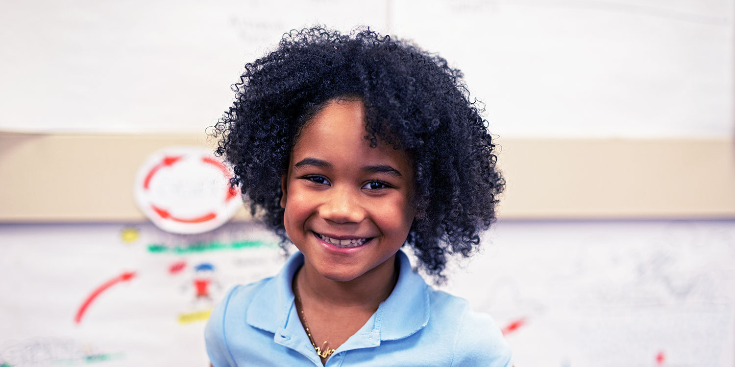 Smiling elementary student standing in front of projects in a classroom.