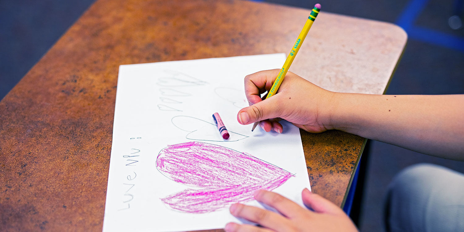 Students hand holding a pencil and drawing a picture with hearts.
